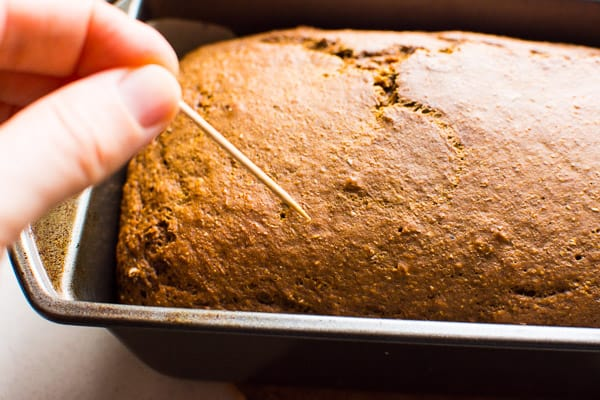 toothpick inserted into baked gingerbread loaf