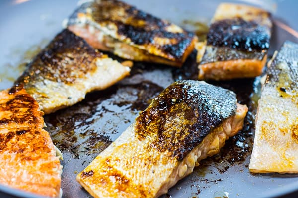 honey garlic salmon with crispy skin on a blue pan