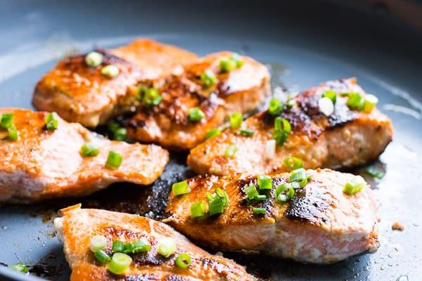 honey garlic salmon on skillet garnished with green onion