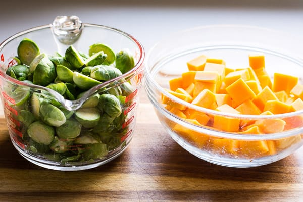 chopped brussels sprouts and butternut squash in separate bowls