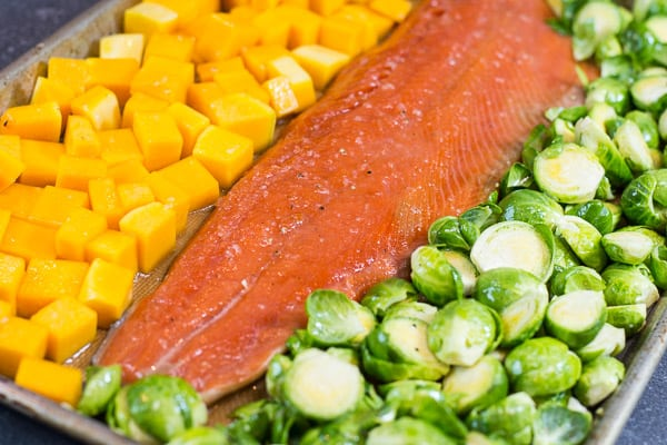 One pan salmon and veggies coated in honey garlic sauce, then baked in a sheet pan for 30 minutes for a healthy easy dinner.