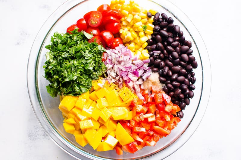 corn, chopped tomato, black beans, mango, red onion, pepper, cilantro in a bowl