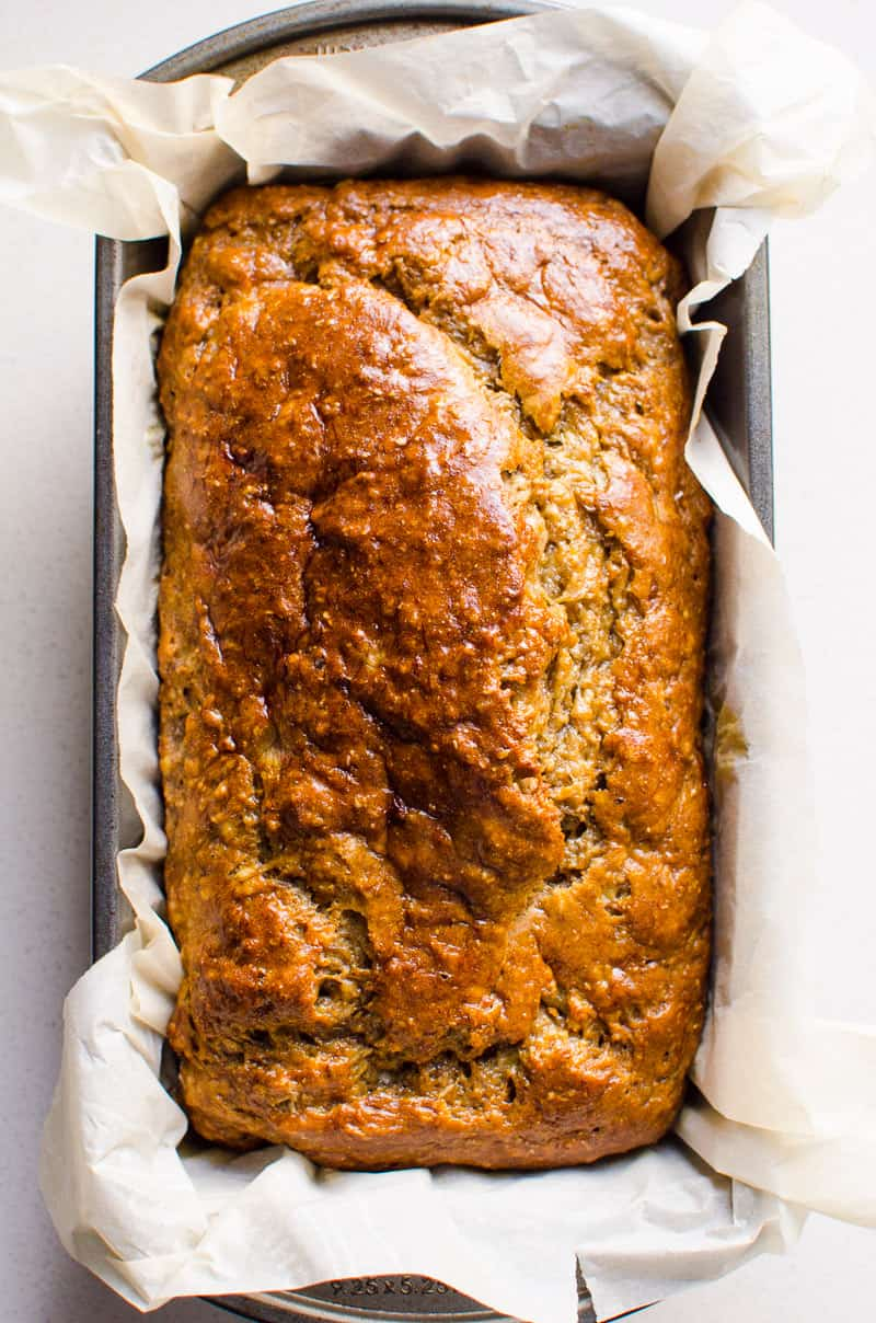 healthy banana bread in a loaf pan lined with parchment paper