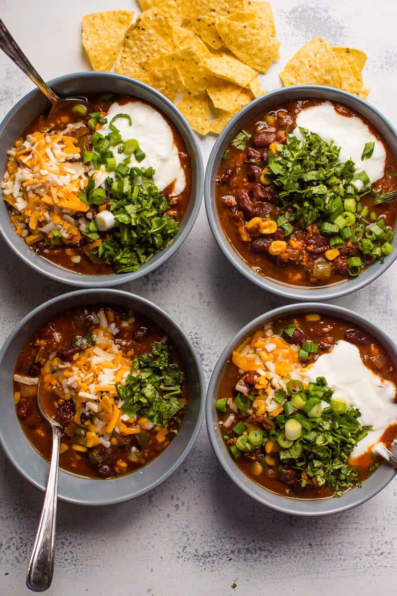 instant pot turkey chili in bowls garnished with cheese, yogurt and tortilla chips