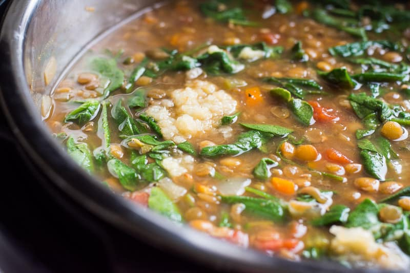 Instant Pot Lentil Soup Recipe is simple and healthy, with only 5 mins of prep. Made in a pressure cooker with green lentils, tomatoes and spinach, then served with Parmesan cheese.