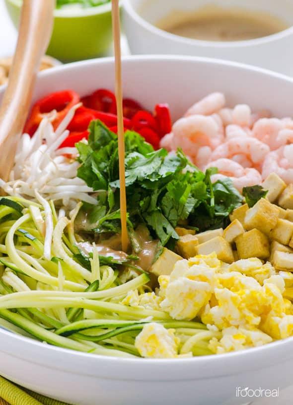 Pouring peanut sauce over Pad Thai Zucchini Noodles Salad