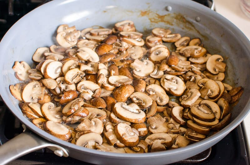 Sauteed brown mushrooms in a skillet.