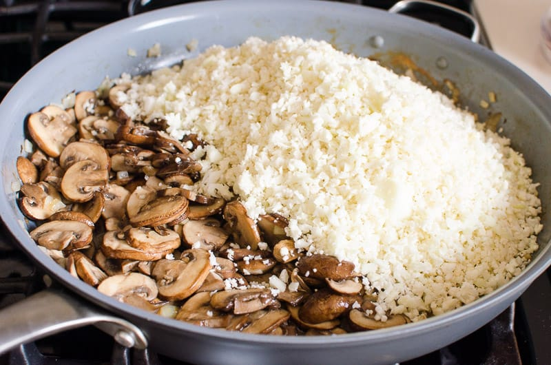 Mushrooms and riced cauliflower in a skillet.