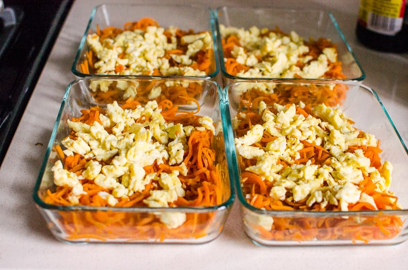 4 glass container with sweet potato noodles topped with scrambled eggs
