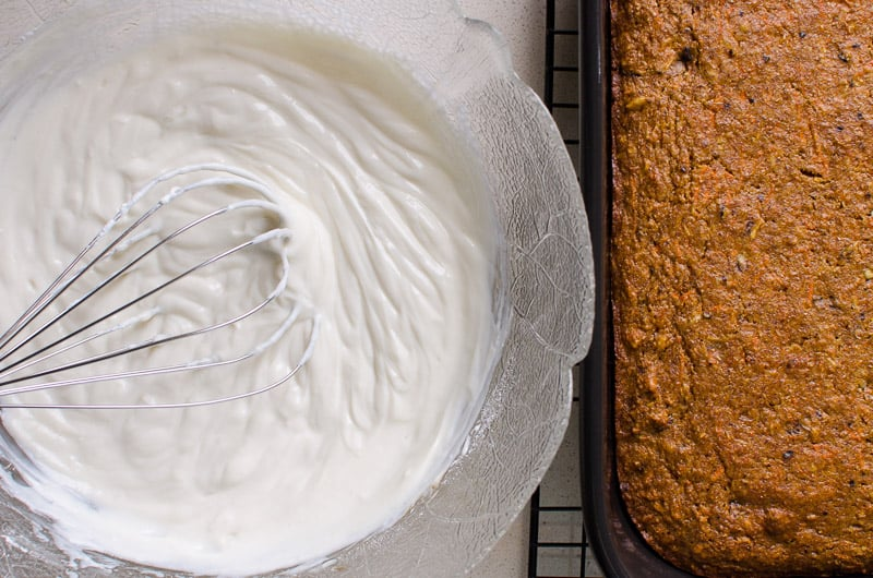 Moist Healthy Carrot Cake Recipe with whole wheat flour, Greek yogurt, toasted coconut and walnuts. Baked, frosted and served all in one pan.