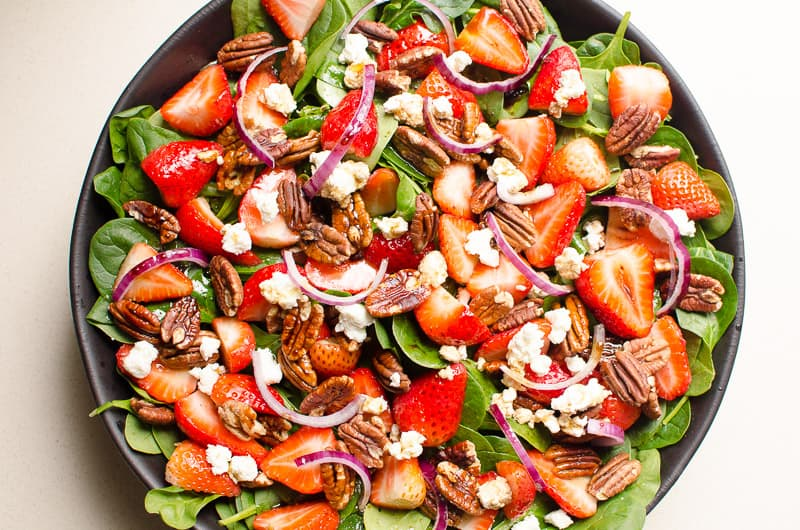 Healthy Strawberry Spinach Salad Recipe with toasted pecans, feta or goat cheese, strawberries, spinach, red onion and super simple balsamic dressing. Takes 10 minutes and everyone will rave about this salad!