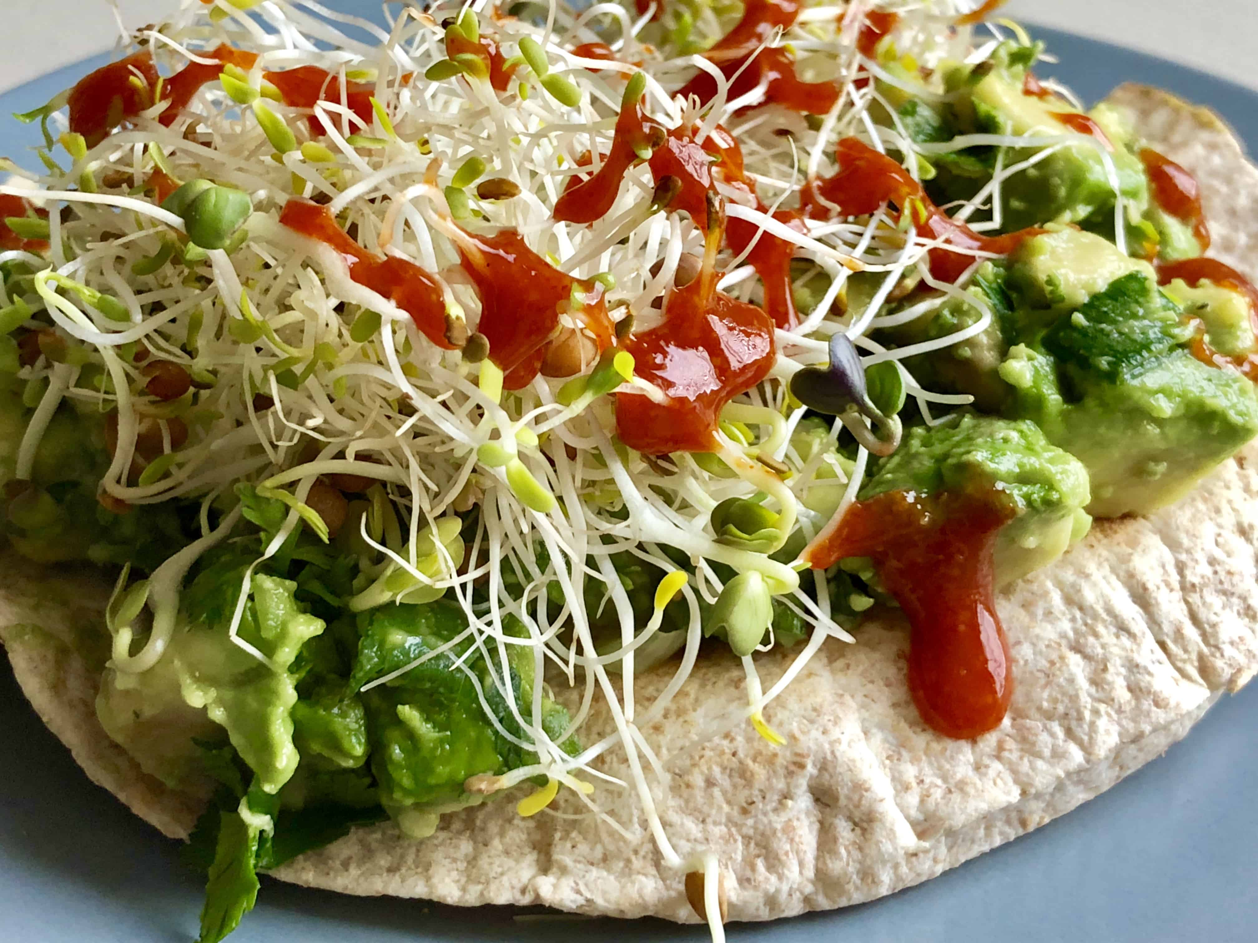 simple avocado salad on tortilla with bean sprouts and hot sauce