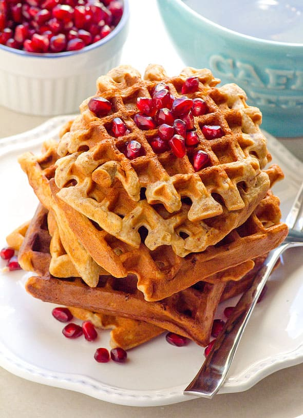 stack of almond flour waffles on a white plate topped with pomegranate arils