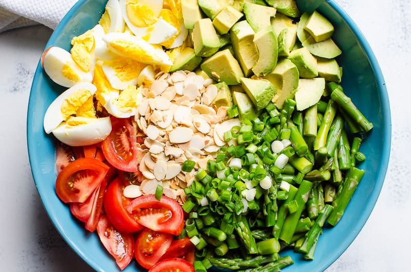 Asparagus Salad Recipe with tomato, avocado, eggs, toasted almonds and super easy dressing mixed together.