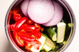 raw red onion, pepper, zucchini in a bowl