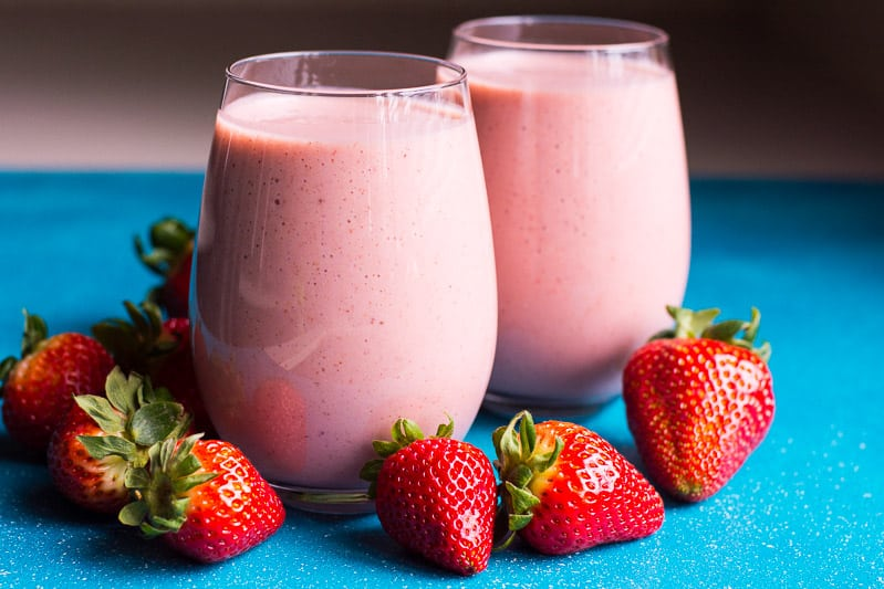 two glasses with strawberry smoothie and fresh berries nearby