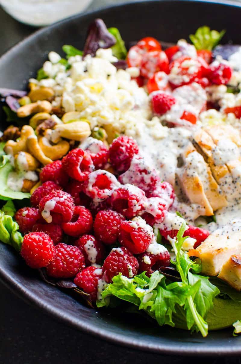 grilled chicken salad with raspberries, nuts, feta cheese and healthy poppy seed dressing
