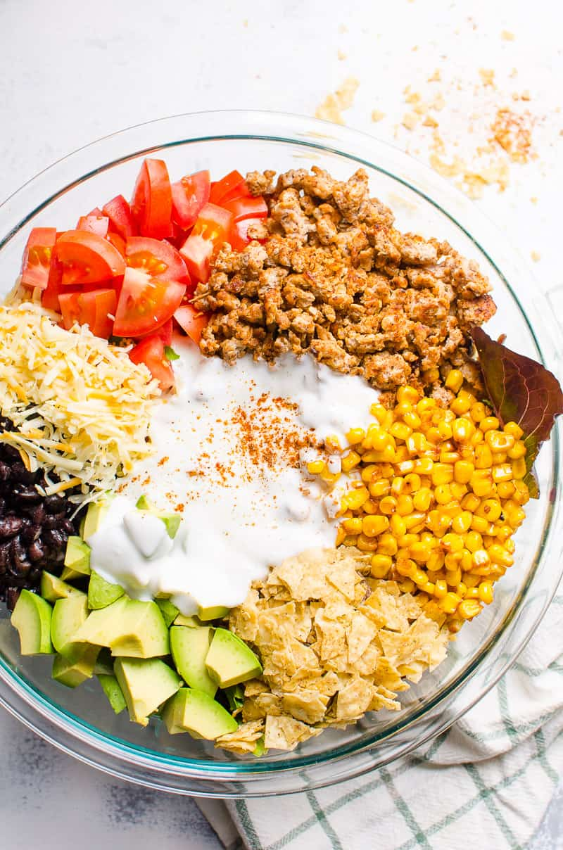 Healthy Taco Salad ingredients in a bowl include avocado, black beans, ground turkey, corn, greens, chips and yogurt