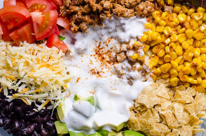 Healthy Taco Salad Ingredients of tomatoes, cheese, black beans, avocado, ground beef, corn, tortillas and dressing
