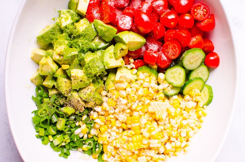 corn, tomatoes, cucumber, avocado, green onion and lime in white salad bowl