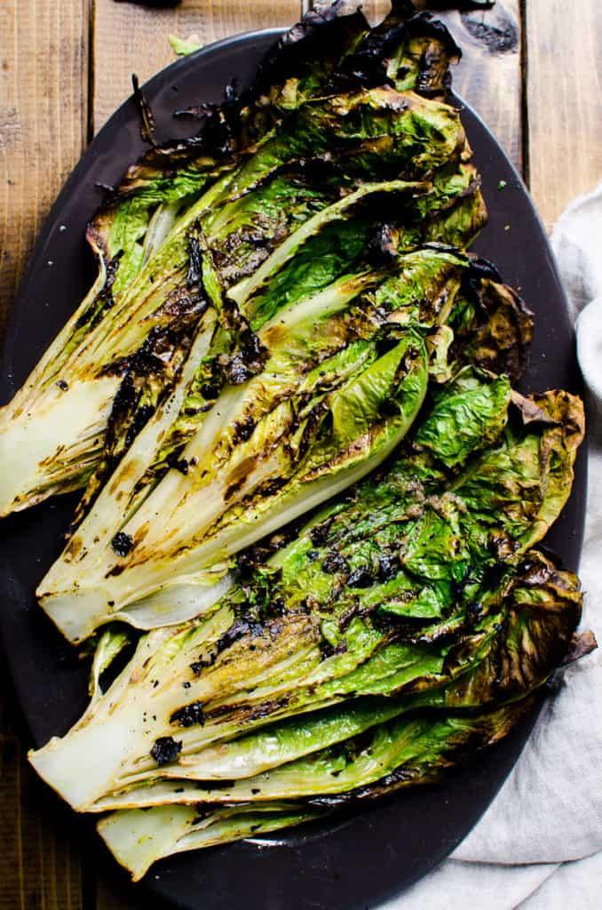 grilled romaine lettuce on black platter