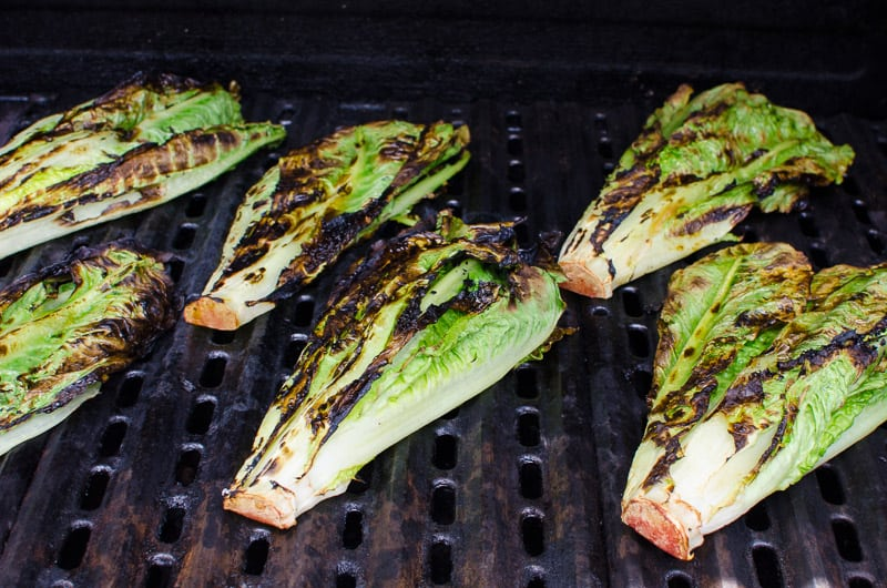 In this 10 minute Grilled Romaine Lettuce Recipe hearts of romaine are grilled, then brushed with magic 3 ingredient sauce everyone will want recipe for. Easy way to eat more veggies!
