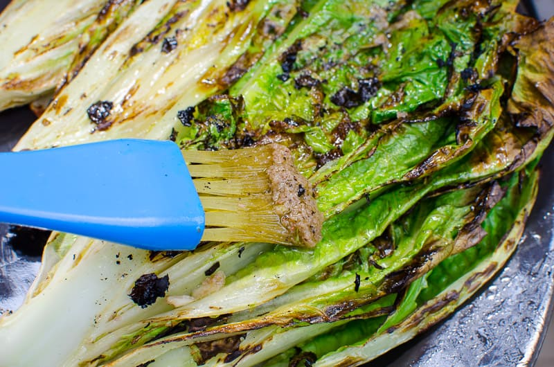 brushing romaine hearts on grill with sauce