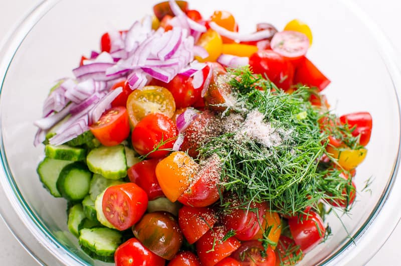 A bowl with cucumber tomato dill salad