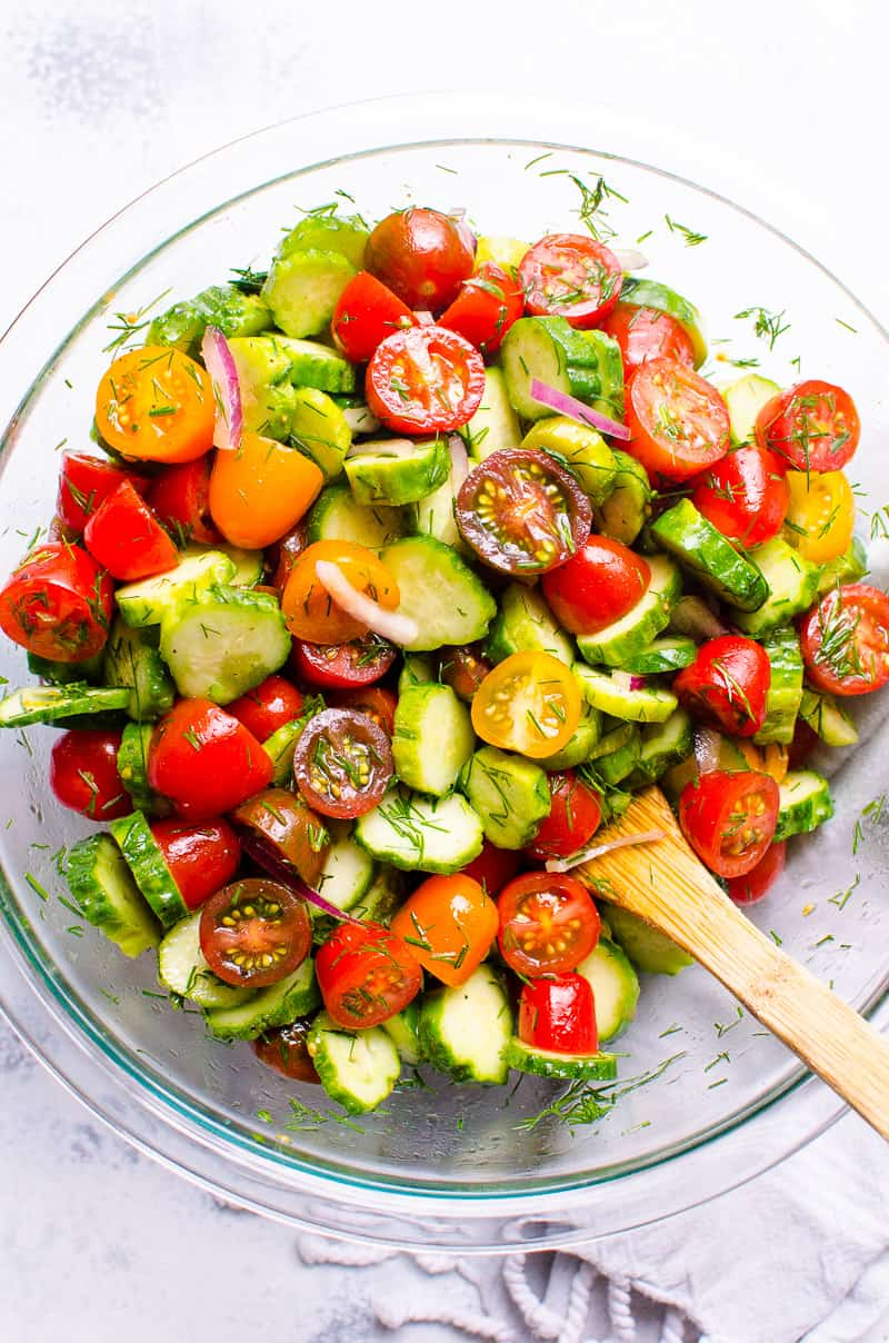 A bowl with halved grape tomato, sliced cucumber, dill onion and cucumber tomato salad dressing.