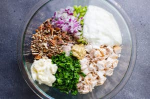 Healthy Chicken Salad ingredients in a glass bowl include chicken, mayo, yogurt, onion and herbs and nuts