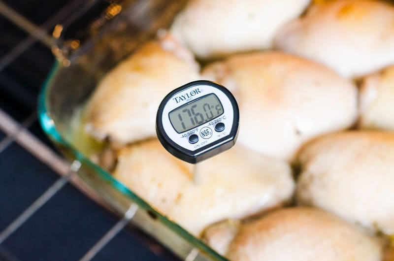 measuring internal temperature with food thermometer of baked chicken thighs