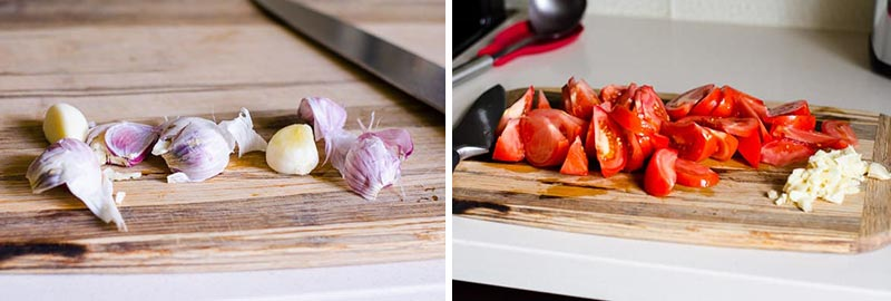 garlic cloves and sliced tomatoes on a cutting board