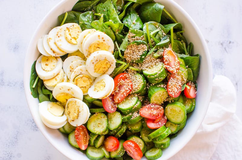 healthy spinach salad served in a large white bowl