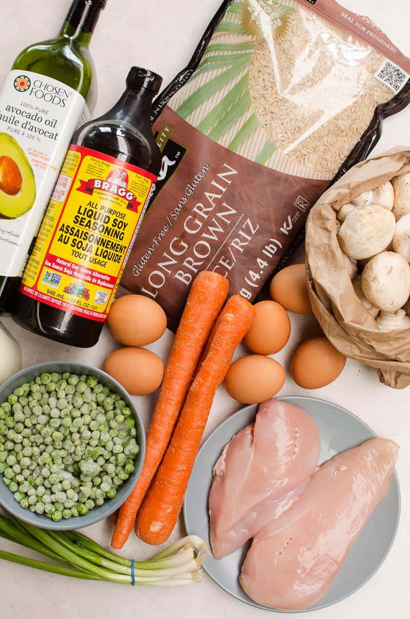 ingredients for Instant Pot Fried Rice including soy seasoning, long grain rice, mushrooms, avocado oil, peas, green onions, chicken breast, carrots and eggs