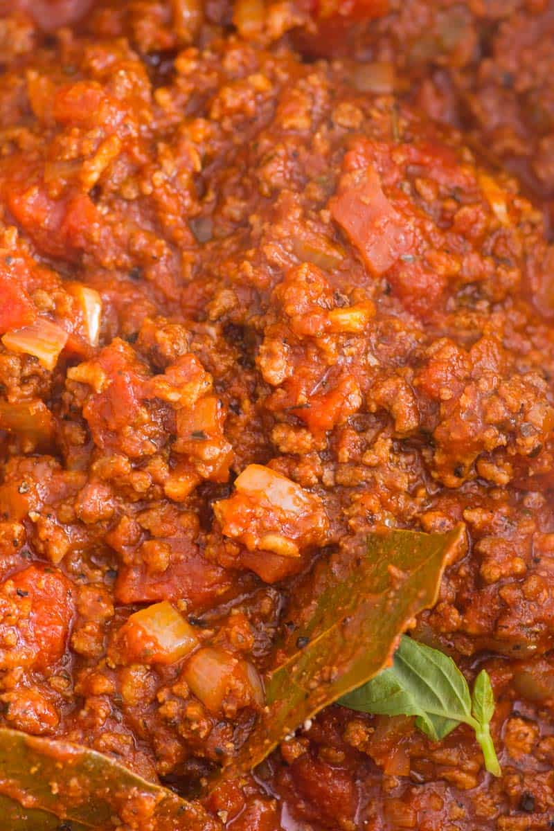 meat sauce recipe closeup with bay leaves and fresh basil