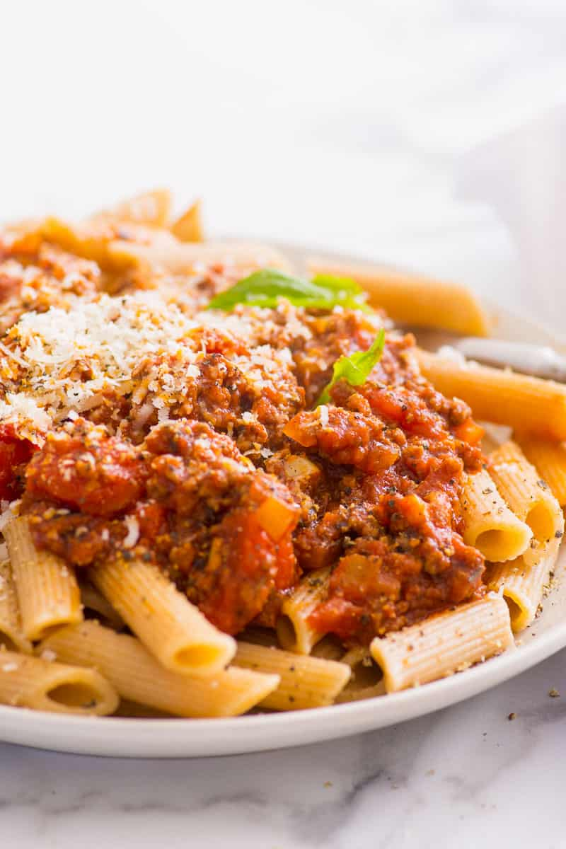 meat sauce served over pasta and garnished with Parmesan cheese on a plate