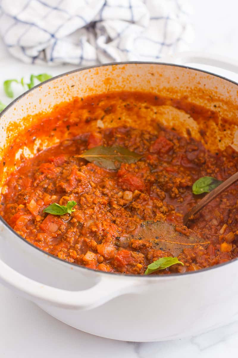 meat sauce garnished with basil in a pot