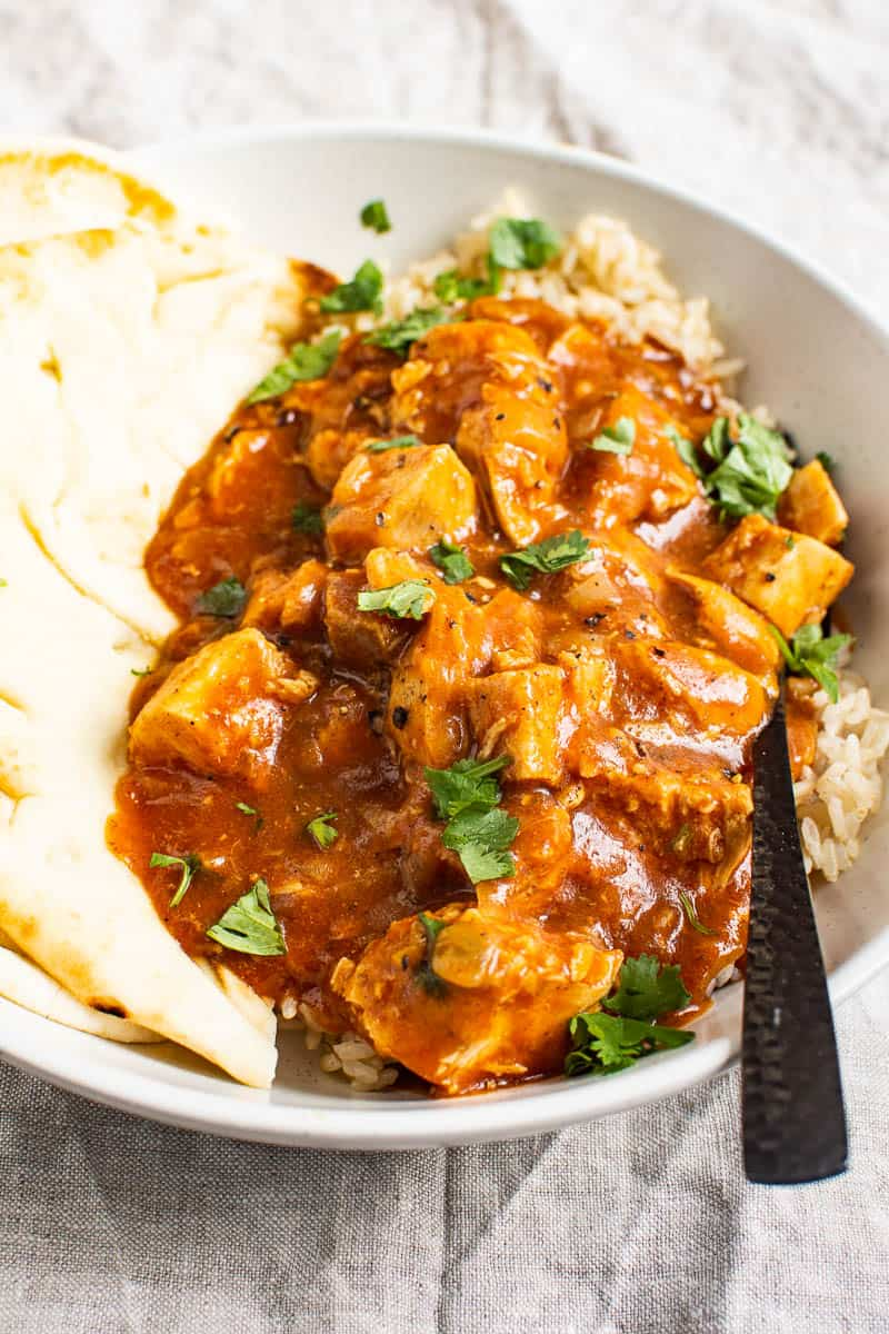 instant pot butter chicken served over brown rice and with naan bread in a bowl