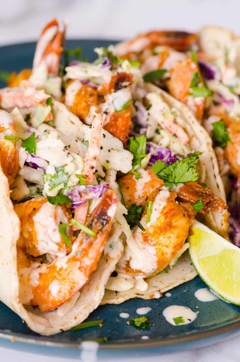 shrimp tacos garnished with sauce and lime