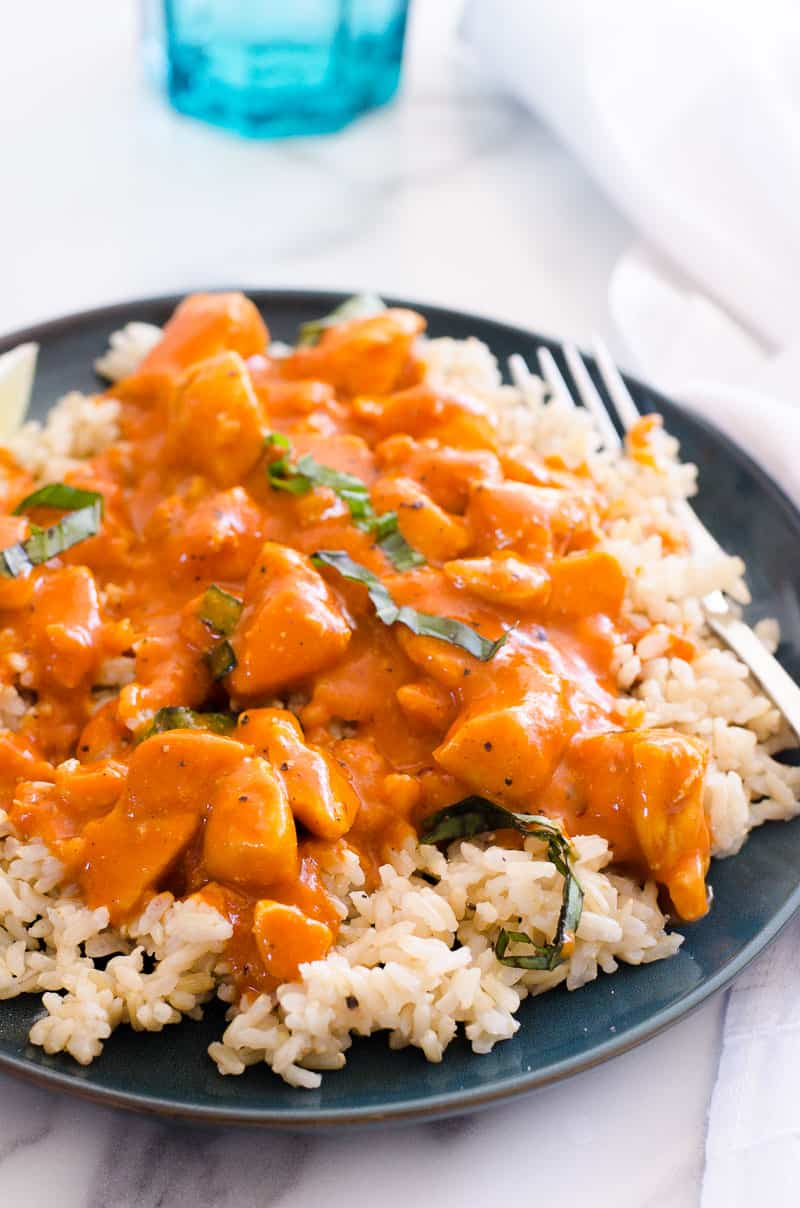 Thai chicken curry served on a bed of brown rice and garnished with basil