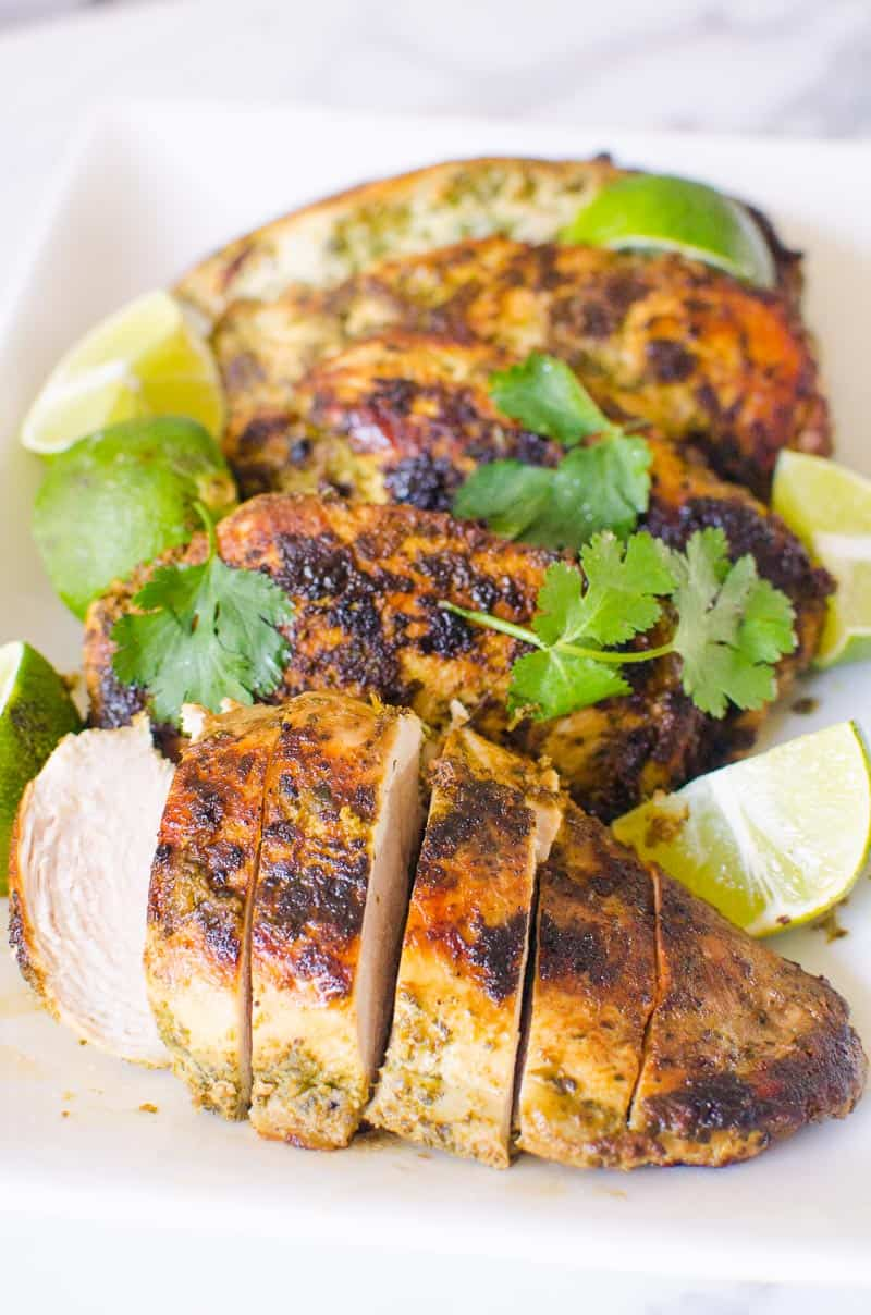 baked, grilled or pan fried cilantro lime chicken garnished with cilantro and limes