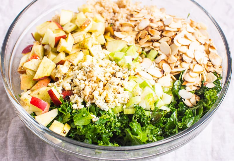 kale, nuts, apple, cheese in a bowl