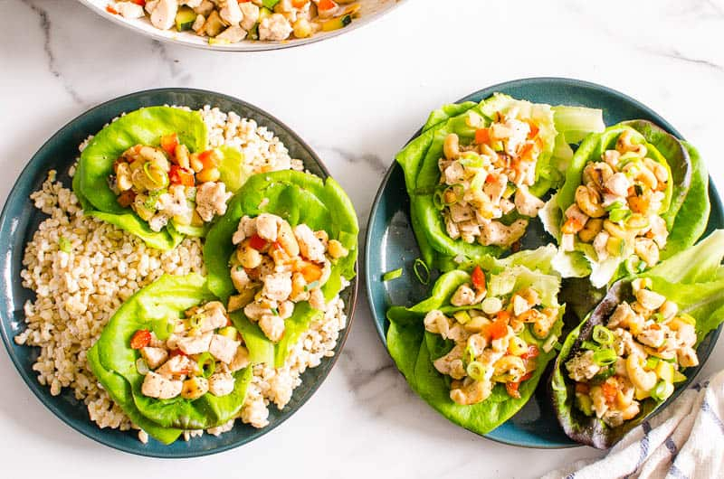 Healthy Chicken Lettuce Wraps served on plates. One plate of lettuce wraps served over brown rice.