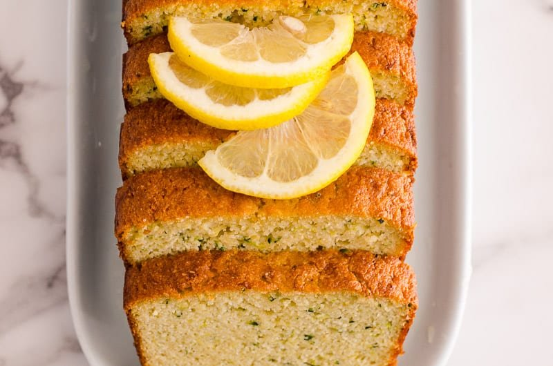 healthy lemon zucchini bread sliced on a white plate garnished with slices of lemon