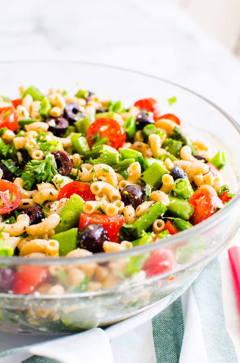 healthy pasta salad with olives, tomatoes, peas and parsley