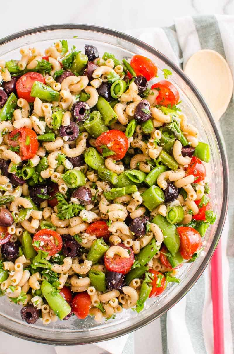 healthy pasta salad in a bowl with wooden spoon on a towel