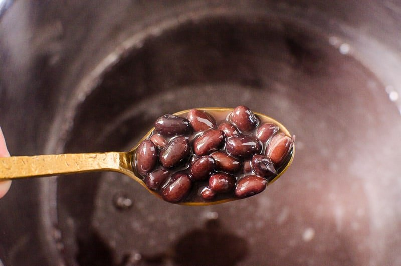 cooked black beans in Instant Pot on a spoon