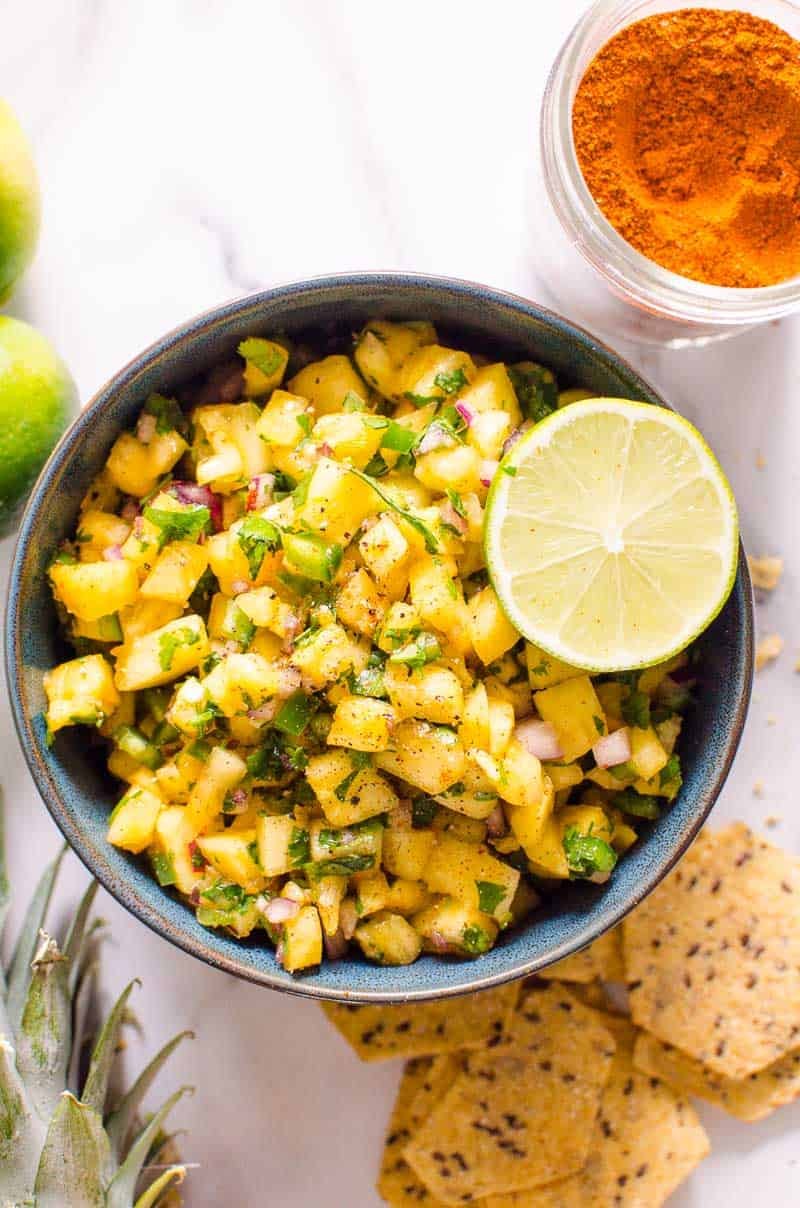 pineapple salsa in a bowl garnished with lime and chips