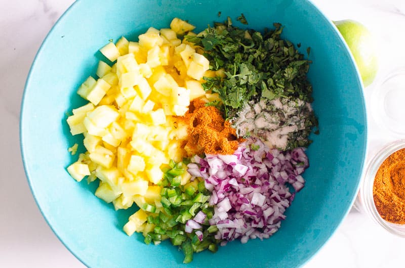 diced pineapple, limes, cilantro, red onion, jalapeno in a bowl