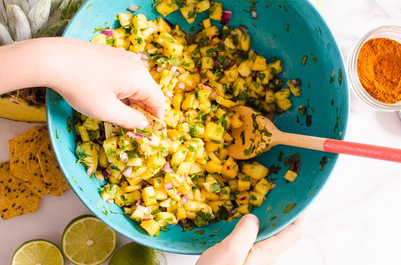 hand scooping pineapple salsa with a chip
